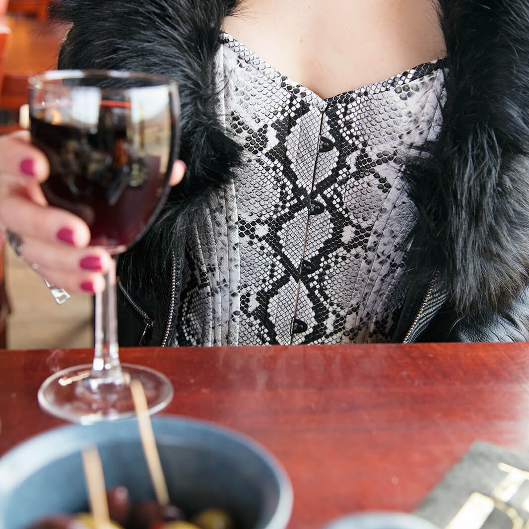 Woman in Corset with Glass of wine and fur coat