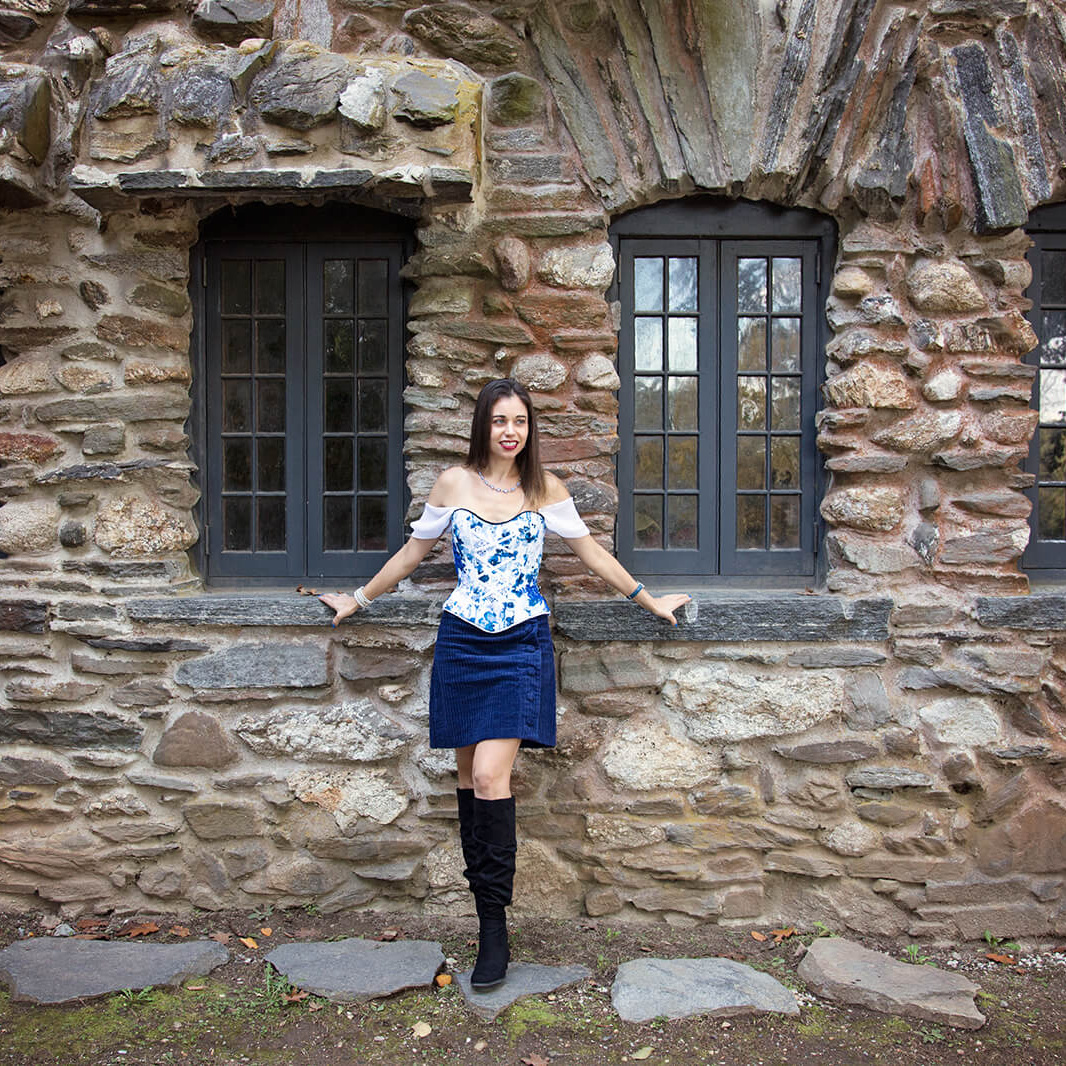 Woman in Off-Shoulder Corset standing in front of stone building