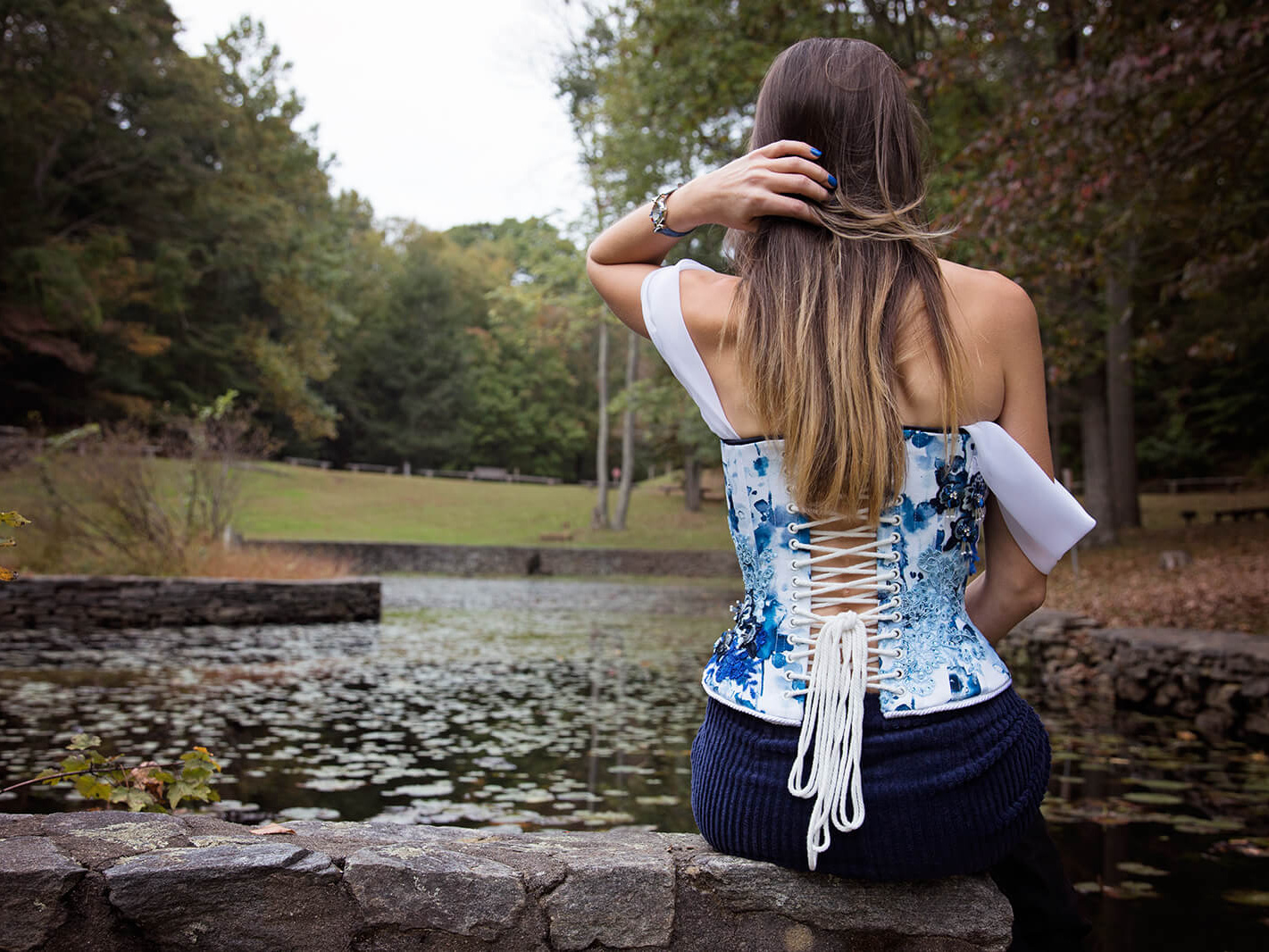 Woman in Off-Shoulder Corset sitting on stone near water