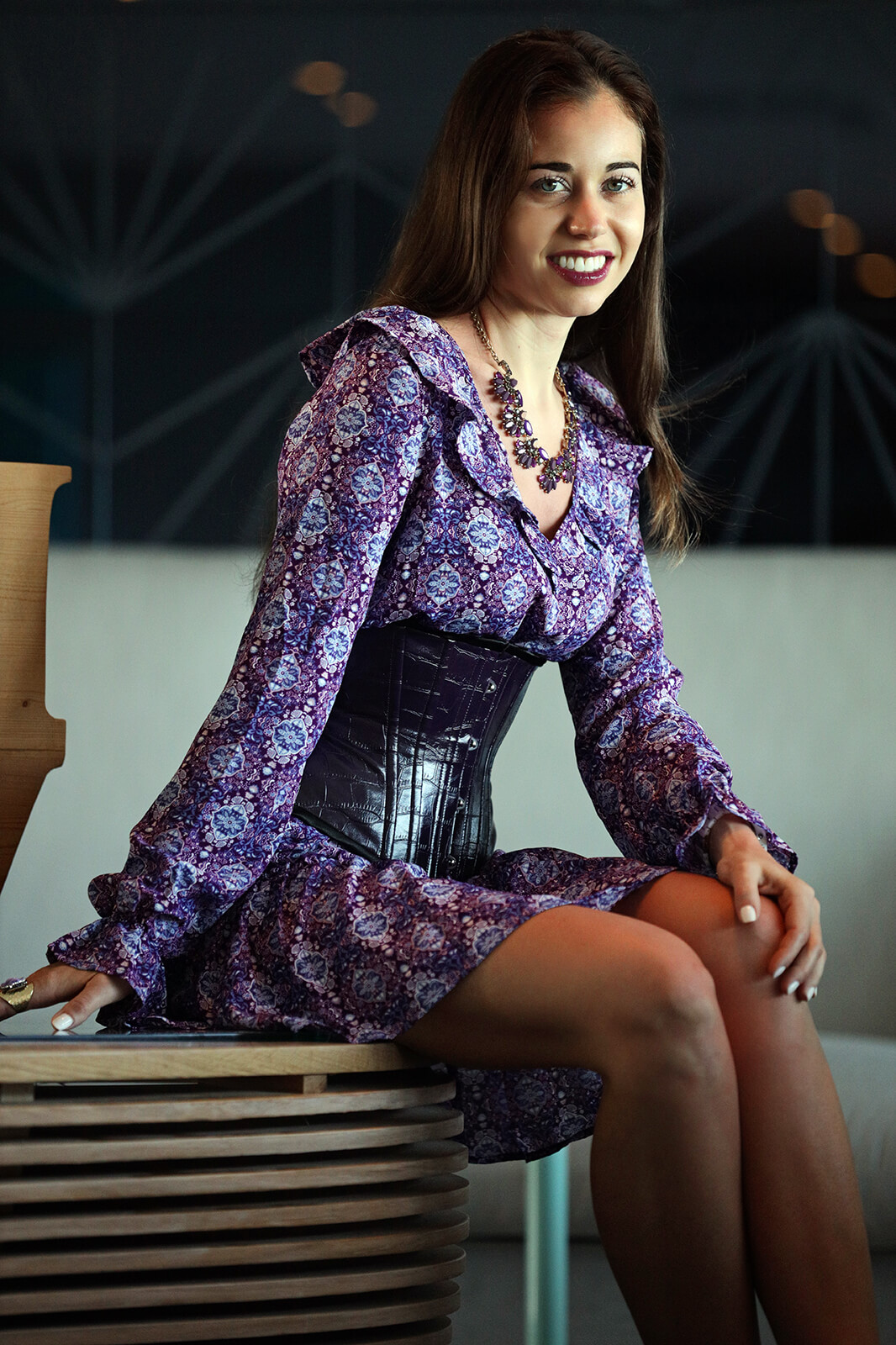 Stella in underbust corset and blue dress sitting on wooden coffee table