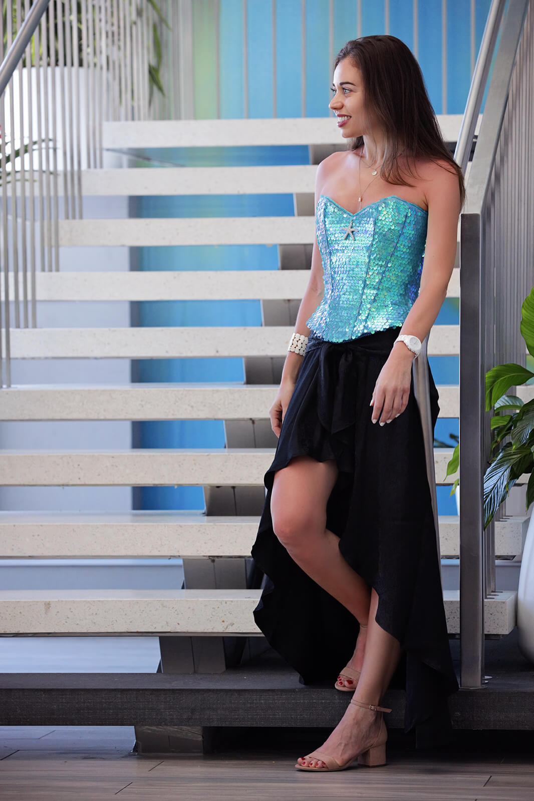 Stella in Sea inspired corset and black dress in front of staircase