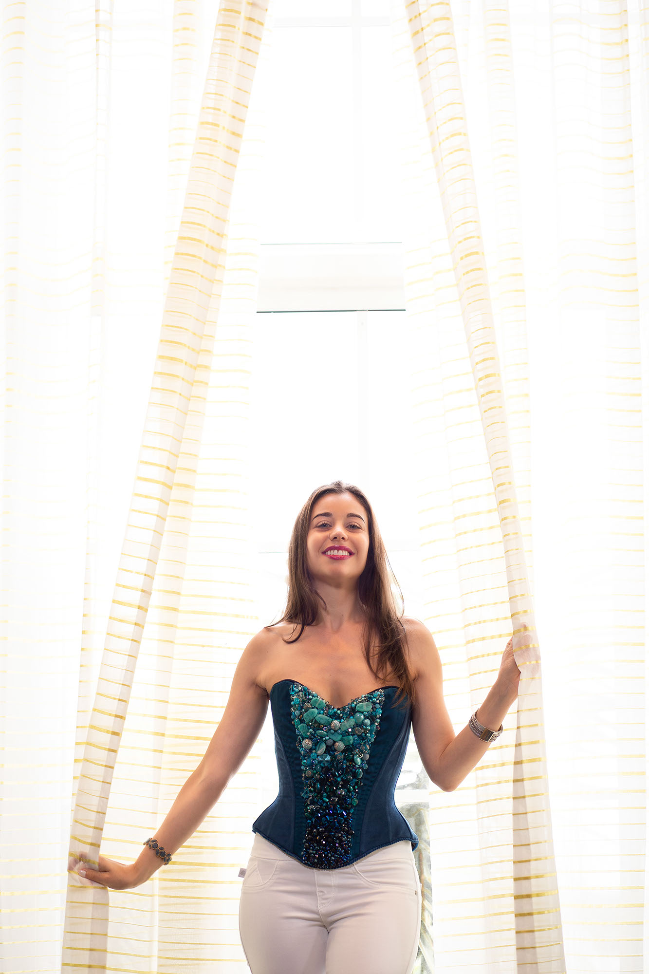 Stella in blue corset in front of window with white curtains