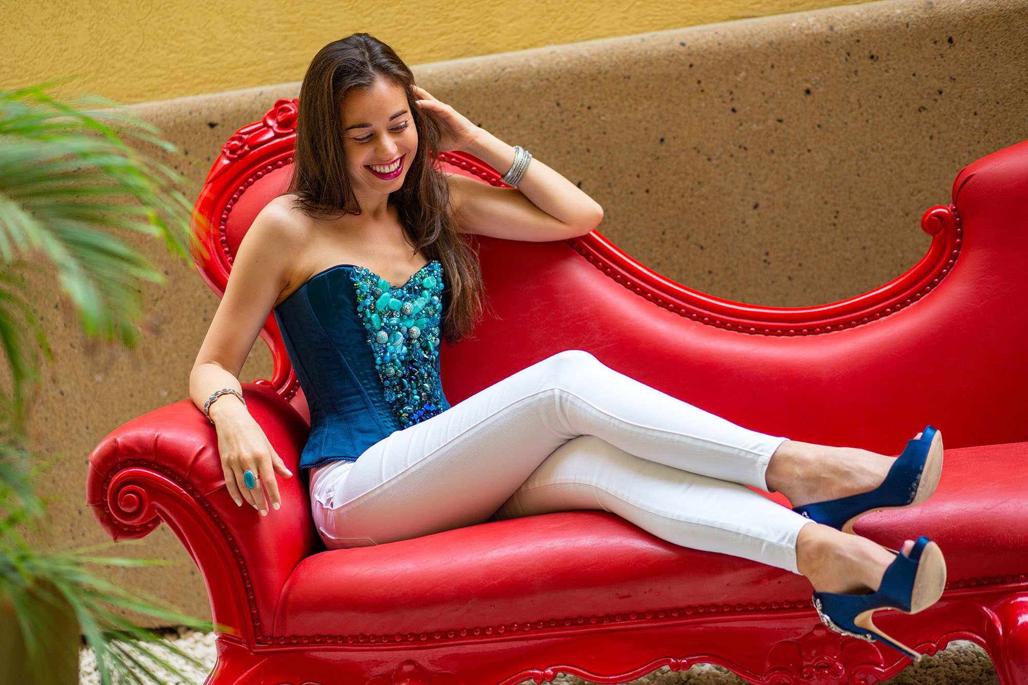Stella in blue corset on red couch