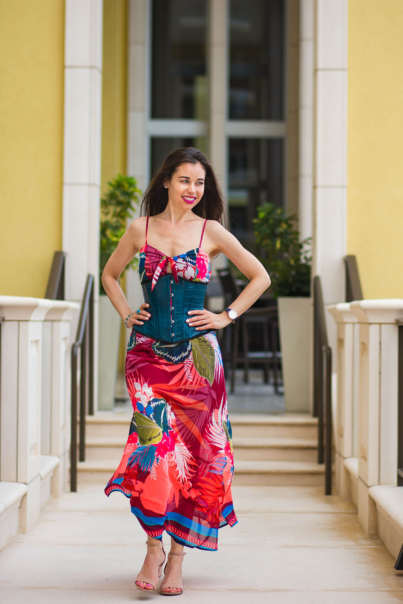 Stella in Teal Corset and Red Tropical Dress with Hands on Her Hips