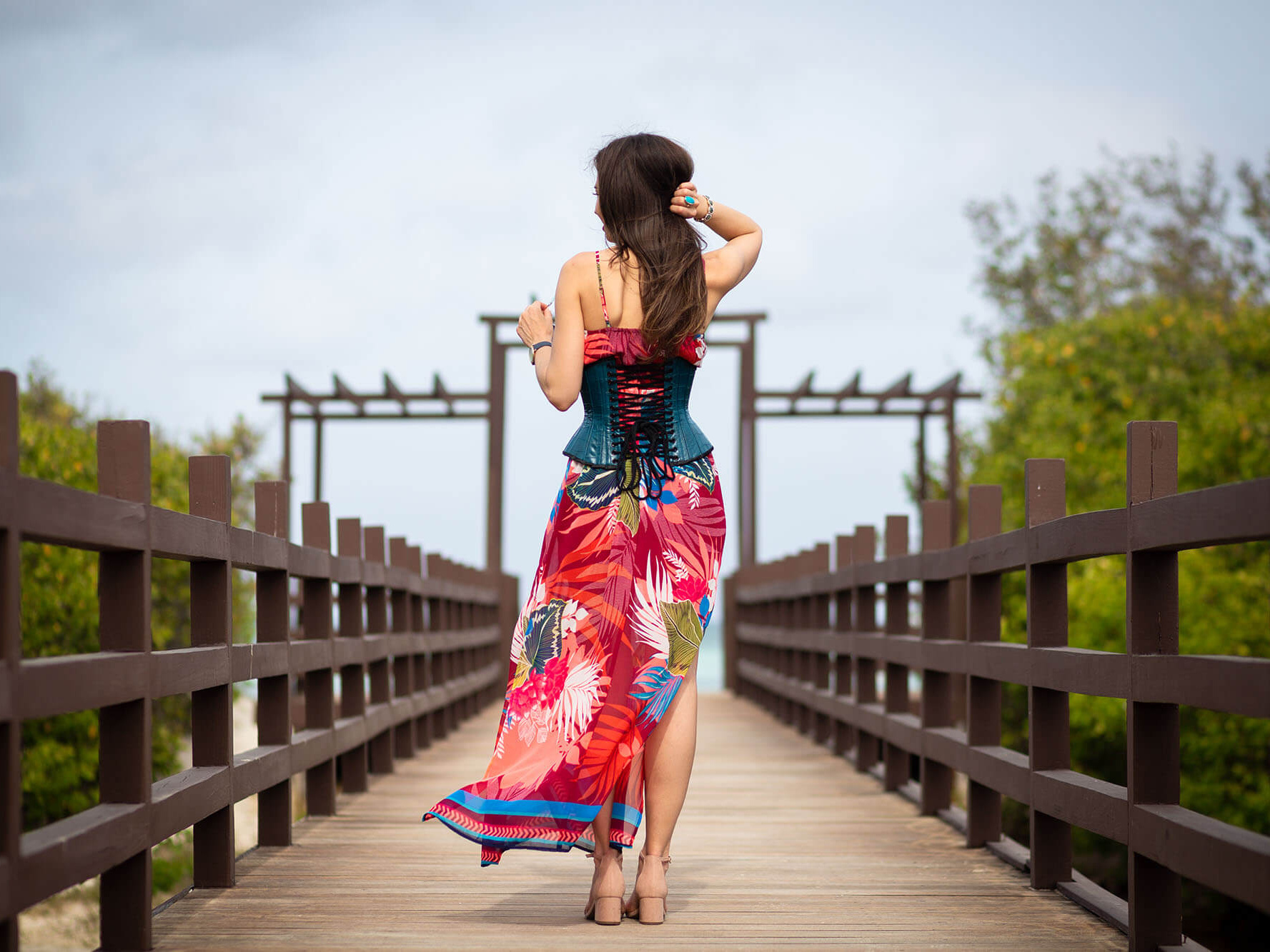 Back View of Stella in Teal Corset and Red Tropical Dress on Wooden Walkway