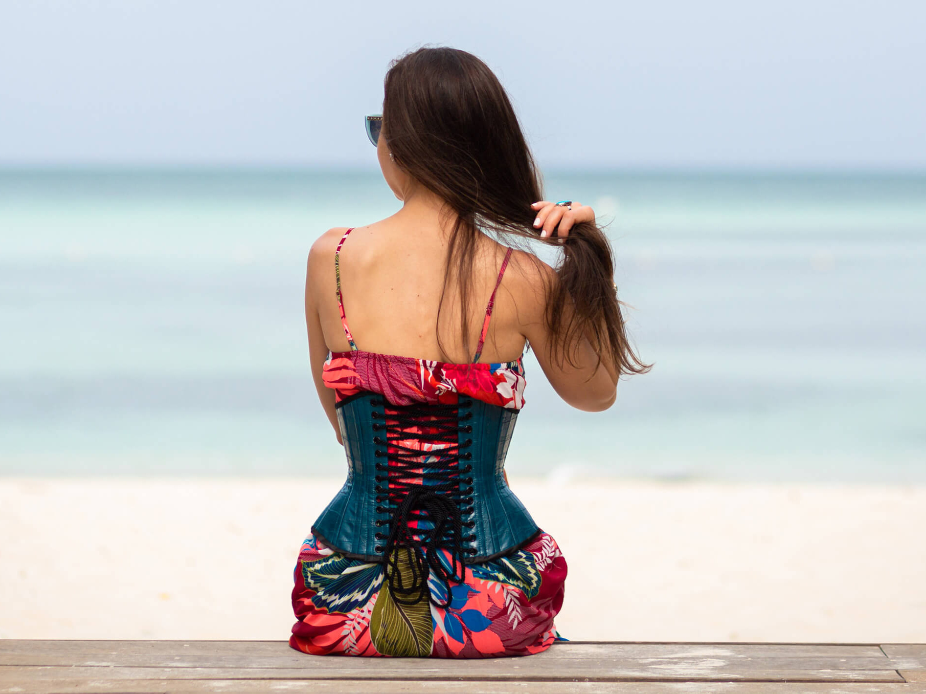 Back view of Stella in Teal Corset and Red Tropical Dress Sitting on Wooden Walkway
