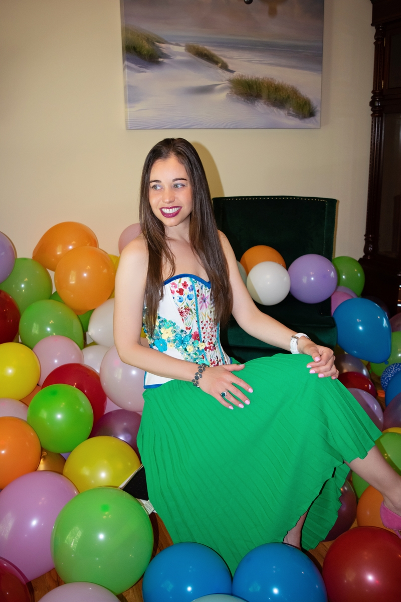 Stella celebrating her birthday surrounded by balloons.