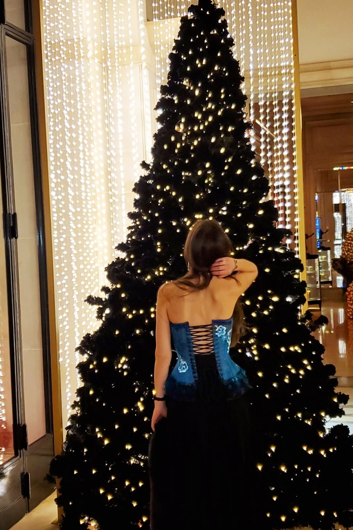 Stella standing in front of a Christmas Tree showing the back of her blue corset.