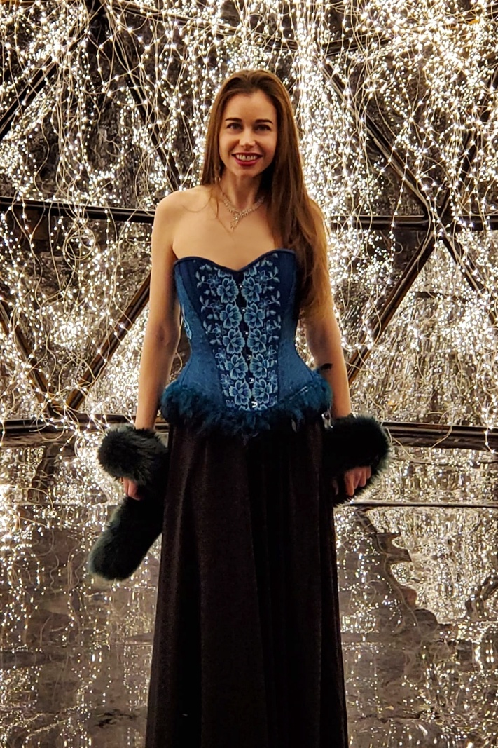 Stella standing in front of string lights wearing a blue corset.